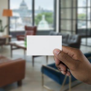 A blank business card held in front of an office space