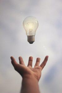 Hand beneath a floating lightbulb